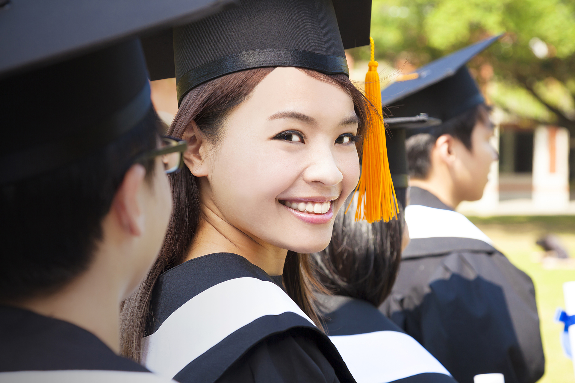 Asian woman standing out from a graduation group smiling