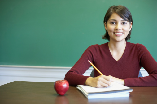 Portrait of a female lecturer sitting at a desk in a classroom