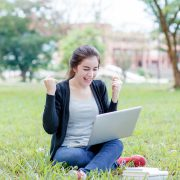 girl looking at her laptop and cheering