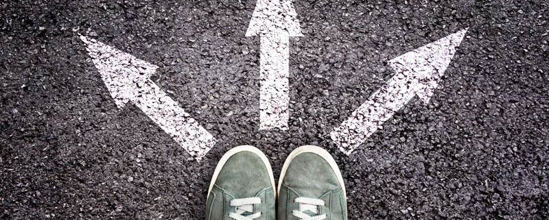 feet on pavement with three arrows showing three different paths to take